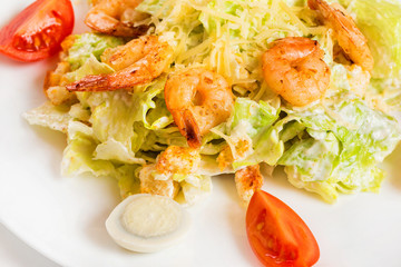 Closeup plate of caesar salad with shrimps isolated at white background.