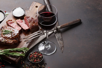 Photo sur cadre textile Viande Grilled ribeye beef steak with red wine, herbs and spices