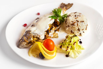 Gefilte fish decorated with mayonnaise and lemon on plate isolated at white background.