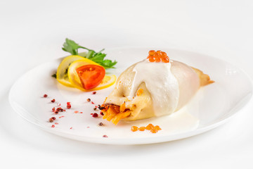 Steamed calamari filled with vegetables decorated with red caviar isolated at white background.
