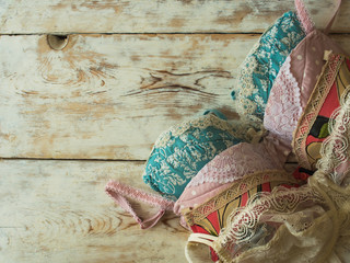 Elegant women's bras laying on the wooden background.