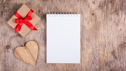 Notepad with blank page, a wooden heart and small gift box with a red bow. Copy space.