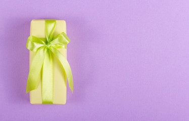 Yellow gift box with a green bow on a purple background. Copy space