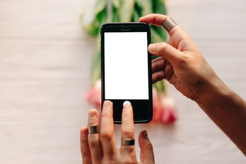 instagram photographer, blogging workshop concept. hand holding phone with empty screen with space for text. pink tulips on white wooden rustic background.