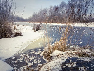 Winter landscape with small river in countryside.