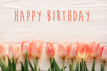 happy birthday text sign on pink tulips on white rustic wooden background flat lay. spring top view of flowers in soft morning light with space for text. greeting card concept
