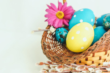 colorful easter eggs in a basket on white background