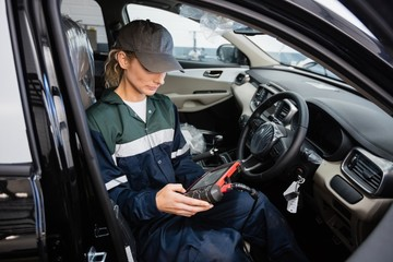 Female mechanic using electronic diagnostic device