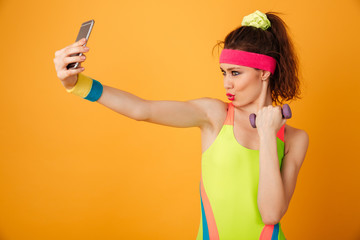 Happy playful young woman athlete holding dumbbell and taking selfie