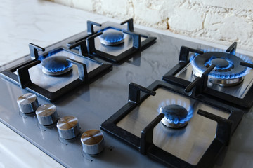 Cooktop with burning gas ring. Gas cooker with blue flames.