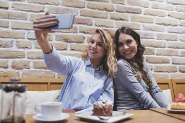 Two pretty women taking selfie at coffee shop.