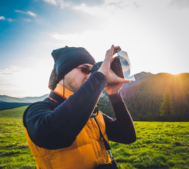 Nature photographer tourist with camera taking a photo in the mountains. Dreamy sunset landscape, spring green meadow and mountain top in the background