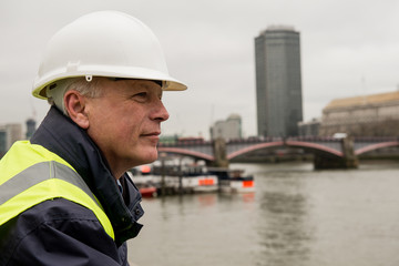 Construction businessman looking across the River Thames, London, UK.