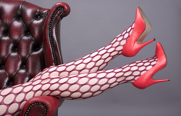 Woman's legs in tights resting on the arm of a leather chair