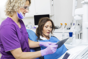 Assistant Showing Report To Patient On Digital Tablet In Dentist