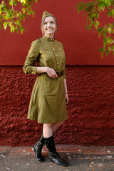 Pretty girl in garrison cap, high boots and Soviet war uniform at red wall