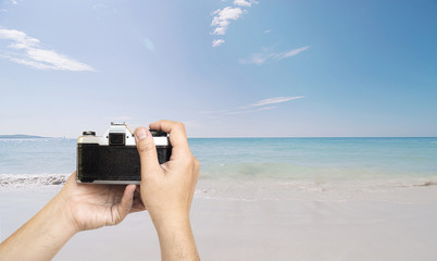 Man holding film camera ready to take photo over sea beach with blue sky background