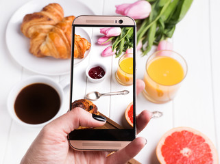Taking photo of delicious breakfast with smartphone