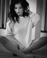 Women in white sweater and tights sitting on the floor.