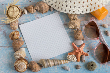 Beach vacation. Different marine items (shells, a starfish), a sheet of paper, sunglasses and sunscreen on blue wooden background.