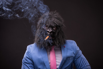 businessman wearing gorilla mask and smoking cigar