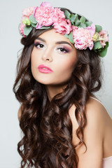 Beautiful Model with Long Curly Hair, Fashion Makeup and Summer Pink Flowers. Young Woman with Flowers Hairstyle