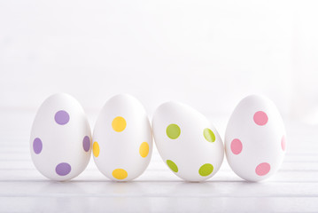 Decorative easter eggs on white wooden table