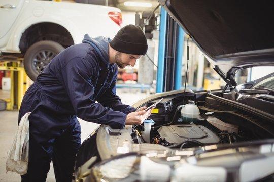 Mechanic using digital tablet on car