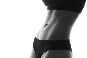 Sexy slim fit woman body abs. Muscled abdomen. Sportswear. Isolated on white. Black and white image