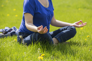 Beautiful blonde eldery senior woman relaxing on a grass in park in yoga meditation. casual outfit