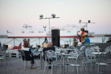 Cafe with a musical scene on the beach of the Sicilian coast on the background of the sea and the white ship sailing