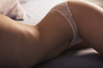 Beautiful sexy woman body in underwear lying on a bed in surves