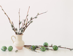 Easter eggs and willow branches on a white background