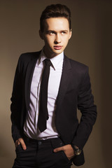 Young handsome brunette macho businessman in black suit and tie. neutral background