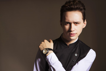Young handsome brunette macho businessman in black suit and white shirt. neutral background