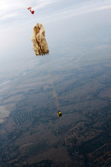 Paratrooper is opening a parachute.