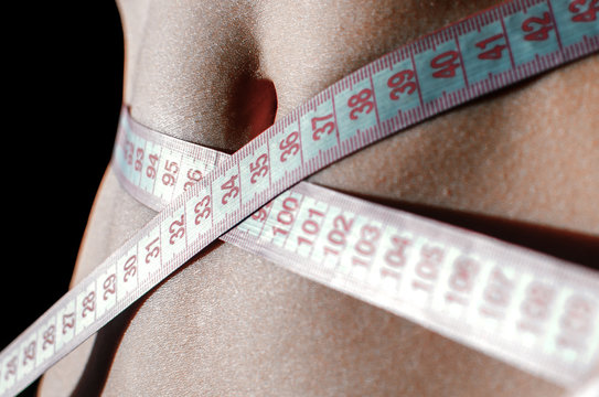 fitness symbols - woman belly with tape measure