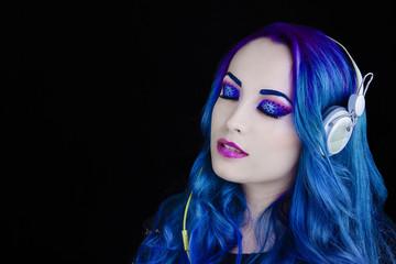 Portrait d'une jolie fille aux cheveux bleu écoutant de la musique les yeux fermés