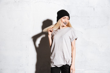 Happy woman in hat with gothic makeup standing and smiling