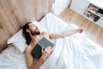 Tired bearded young man with book sleeping in bed