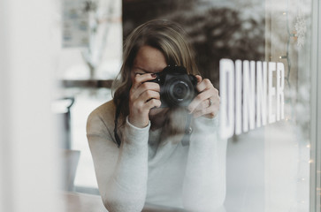 Woman photographing while sitting in cafe seen through glass