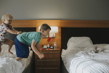 Boy pushing brother jumping from bed at home