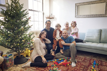 Portrait of smiling family by Christmas tree at home