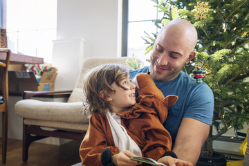 Happy father looking at son dressed in costume against Christmas tree at home