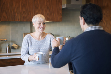 Smiling woman giving mug to man while sitting at table in home