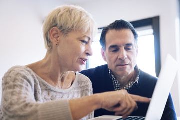 Senior woman showing laptop computer to man at home