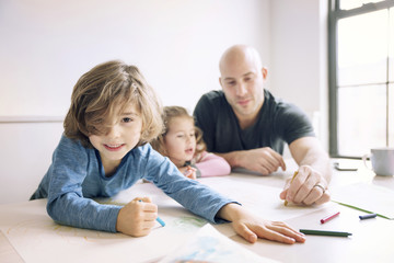 Portrait of boy drawing while father assisting daughter at table in home