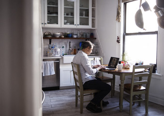 Side view of man using laptop computer while sitting at dining table in kitchen