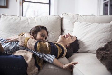 Cheerful mother and daughter enjoying on sofa at home