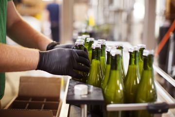 Cropped image of hands arranging beer bottles on conveyor belt at brewery